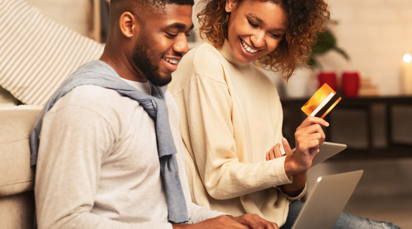 couple online shopping holding credit card