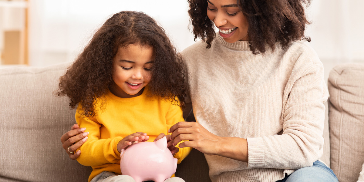 mother with daughter adding to piggy bank