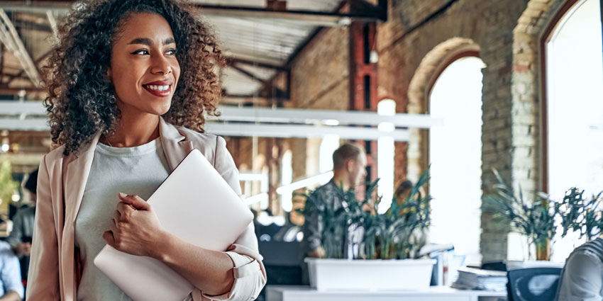 Smiling young woman carrying laptop