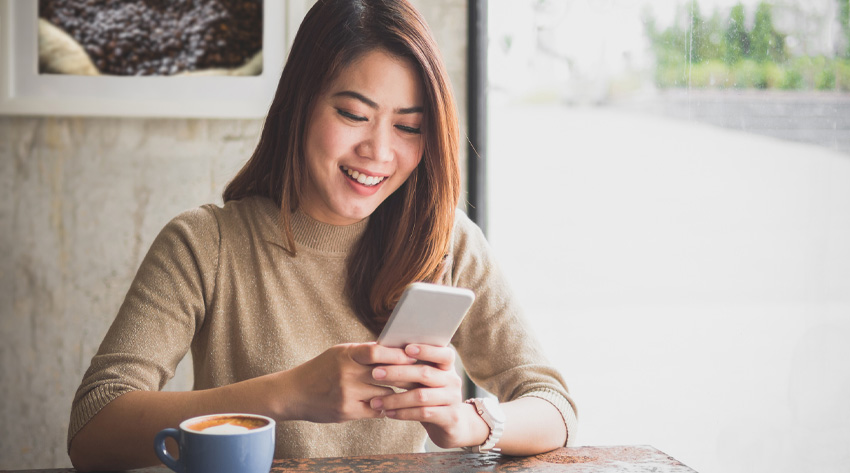 woman in coffee shop using mobile device